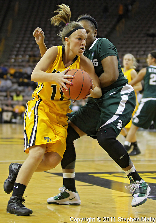 January 27 2010: Iowa guard Trisha Nesbitt (11) drives around Michigan St. guard Porsche Poole (3) during the first half of an NCAA women's college basketball game at Carver-Hawkeye Arena in Iowa City, Iowa on January 27, 2010. Iowa defeated Michigan State 66-64.