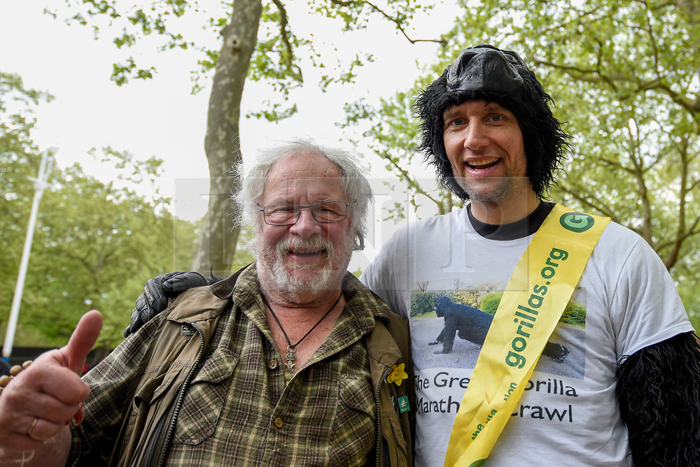 """© Licensed to London News Pictures. 29/04/2017. London, UK. Met Police officer Tom Harrison, 41, known as """"Mr Gorilla"""", celebrates with wildlife presenter Bill Oddie, after finally completing the London Marathon after six days of crawling and raising £23,900 for The Gorilla Organisation.   Photo credit : Stephen Chung/LNP"""