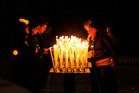 Milan, Italy, Duomo Cathedral. A group of people lighting prayer candles.
