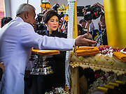 19 OCTOBER 2014 - BANG BUA THONG, NONTHABURI, THAILAND: YINGLUCK SHINAWATRA, former Prime Minister of Thailand, (center) lights the crematorium at Apiwan Wiriyachai's cremation at Wat Bang Phai in Bang Bua Thong, a Bangkok suburb, Sunday. Apiwan was a prominent Red Shirt leader. He was member of the Pheu Thai Party of former Prime Minister Yingluck Shinawatra, and a member of the Thai parliament and served as Yingluck's Deputy Prime Minister. The military government that deposed the elected government in May, 2014, charged Apiwan with Lese Majeste for allegedly insulting the Thai Monarchy. Rather than face the charges, Apiwan fled Thailand to the Philippines. He died of a lung infection in the Philippines on Oct. 6. The military government gave his family permission to bring him back to Thailand for the funeral. His cremation was the largest Red Shirt gathering since the coup.     PHOTO BY JACK KURTZ