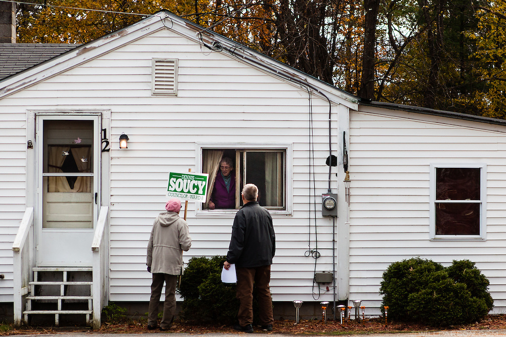 Ward 8 city council candidate Dennis Soucy and his wife Carol Soucy talk with Eileen Shattuck of Concord, New Hampshire, through her window on Sunday, November 3, 2013. Walking at a brisk pace, Soucy passed out 75 campaign flyers on Sunday before running out early in the afternoon.