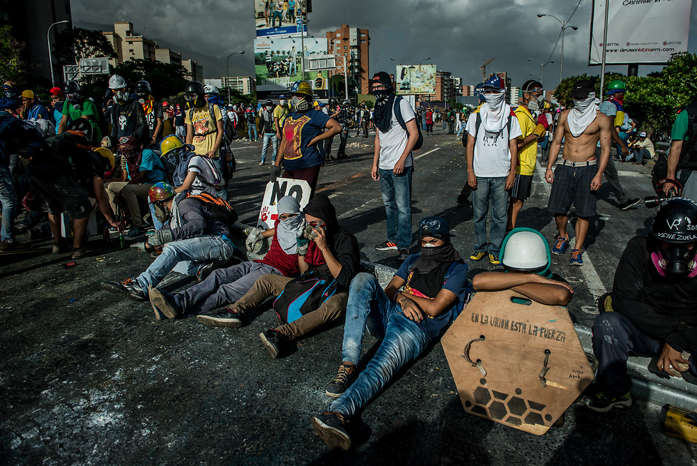 CARACAS, VENEZUELA - MAY 26, 2017:  Anti-government protesters rest during a lull in fighting after taking back control of the main highway that runs through Caracas from government security forces. The streets of Caracas and other cities across Venezuela have been filled with tens of thousands of demonstrators for nearly 100 days of massive protests, held since April 1st. Protesters are enraged at the government for becoming an increasingly repressive, authoritarian regime that has delayed elections, used armed government loyalist to threaten dissidents, called for the Constitution to be re-written to favor them, jailed and tortured protesters and members of the political opposition, and whose corruption and failed economic policy has caused the current economic crisis that has led to widespread food and medicine shortages across the country.  Independent local media report nearly 100 people have been killed during protests and protest-related riots and looting.  The government currently only officially reports 75 deaths.  Over 2,000 people have been injured, and over 3,000 protesters have been detained by authorities.  PHOTO: Meridith Kohut