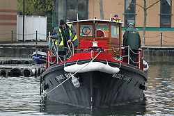 © Licensed to London News Pictures. 13/12/2013. The famous and historic fireboat MASSEY SHAW has returned to London today after a Heritage Lottery funded restoration. The fireboat was built in the 1930s and played a role in the war, helping to evactuate soldiers from Dunkirk and also dealing with fires from the river during the Blitz. The restoration of Massey Shaw was carried out in Gloucester after a lottery award in 2008. She is the oldest operating fireboat in Europe and is listed in the National Historic Fleet. She arrived at West India Dock this morning on a lorry where she was moved by crane in to the water. Video available here http://youtu.be/umLWqealesU Credit : Rob Powell/LNP