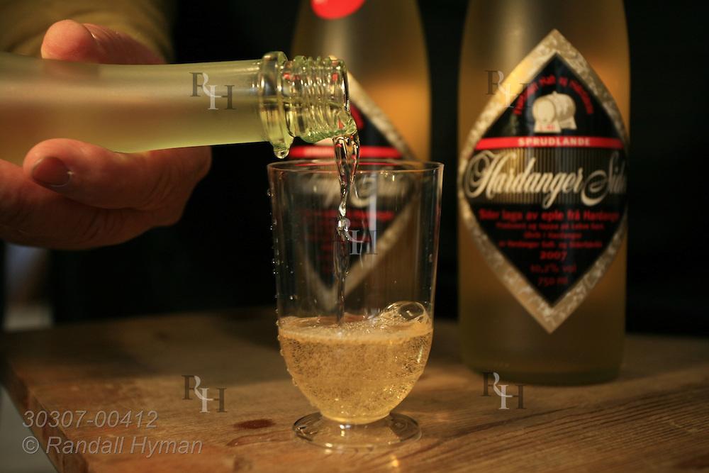 Homemade apple cider is poured into glasses bearing Lekve Gard farm's own label, Hardangersider; Ulvik, Hardangerfjord, Norway.