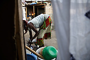 Aminata Nombre, 34, who is HIV positive, does dishes outside her home in the Campement neighborhood of Abidjan, Cote d'Ivoire on Wednesday July 10, 2013. Aminata is under ARV treatment and takes three pills every day.