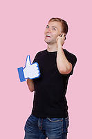 Cheerful young man using cell phone while holding fake like button over pink background