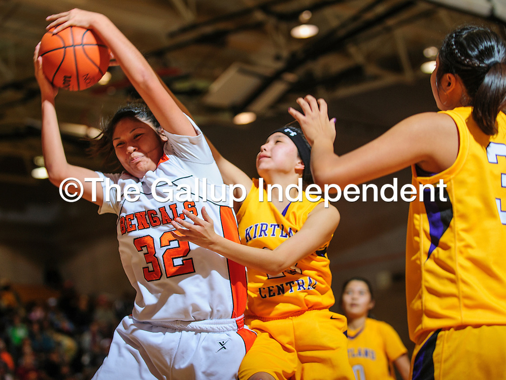 010512  Adron Gardner<br /> <br /> Gallup Bengal Cheyenne Livingston (32), left,  collects a rebound ahead of Kirtland Central Bronco Shamika Benally (23) at Gallup High School Saturday.