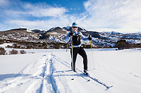 A middle aged woman cross country skiing on the foothills of the La Sal Mountains in southeast Utah, USA.