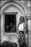 Bangladesh.  Mother and child with a friend at a window. Near Dhakha.