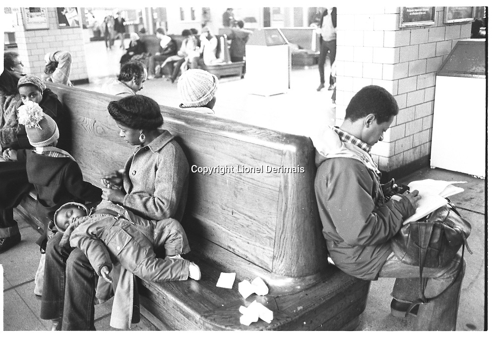 Black boy sleeping on his mother's lap in Staten Island ferry terminal, New York City. Street photography. 1980