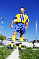 Portrait of professional soccer player in uniform posing with ball on field