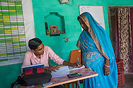 Jeevika Field Associate Raju Kumar (in pink shirt) issues a receipt to a producer group farmer in the collection centre in Machahi village, Muzaffarpur, Bihar, India on October 27th, 2016. Non-profit organisation Technoserve works with women vegetable farmers in Muzaffarpur, providing technical support in forward linkage, streamlining their business models and linking them directly to an international market through Electronic Trading Platforms. Photograph by Suzanne Lee for Technoserve