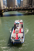 A sightseeing boat along the Chicago River looking toward the Wabash Bridge during summer in Chicago, Illinois, USA