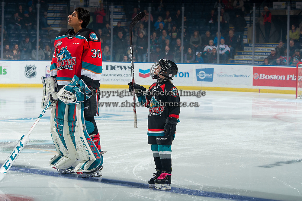 KELOWNA, BC - NOVEMBER 8: The minor hockey player of the game lines up with Roman Basran #30 of the Kelowna Rockets against the Medicine Hat Tigers at Prospera Place on November 8, 2019 in Kelowna, Canada. (Photo by Marissa Baecker/Shoot the Breeze)