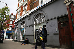 © Licensed to London News Pictures. 02/04/2020. London, UK. People wearing face masks walk past a branch of Barclays Bank in Haringey, north London which is closed following coronavirus lockdown. The former Governor of the Bank of England, Lord King of Lothbury, has said that bank branches should reopen to ensure that businesses are able to access the emergency funding on offer from the Government. Photo credit: Dinendra Haria/LNP