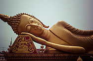 Reclining gilded buddha in Wat That Luang Tai, south of Pha That Luang, Vientiane, Laos, Southeast Asia