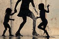 Une femme et des enfants jouent avec de l'eau dans une fontaine lors de la canicule de l'ete. A woman and two children cool off in a public water fountain, in Evian les Bains, France, near the border with Switzerland, Wednesday, July 26, 2006. .(Photo-genic.ch/ OLIVIER MAIRE)