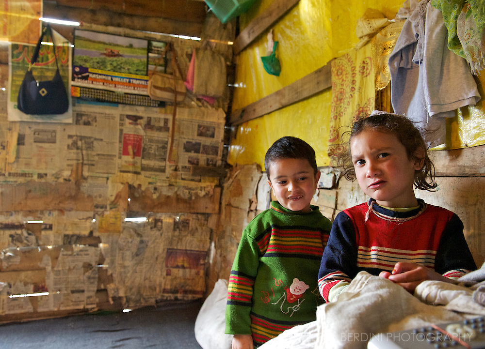 Children play in one room of their pile dwelling built on the Dal Lake. Kashmir. India