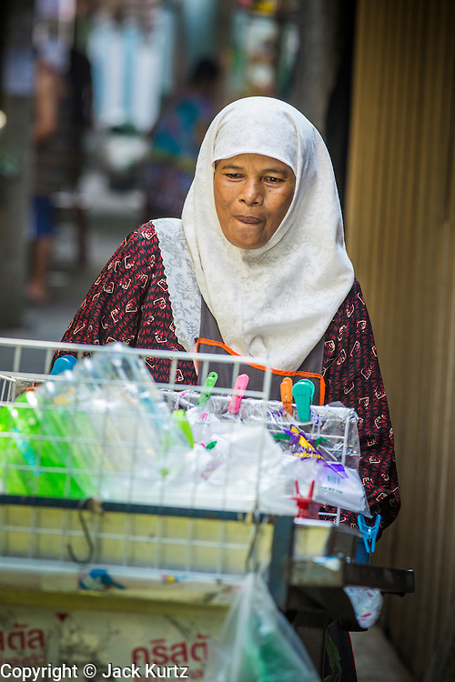 "10 JANUARY 2013 - BANGKOK, THAILAND:      A Muslim woman pushes the snack cart she sells food from through the Baan Krua neighborhood in Bangkok. The Ban Krua neighborhood of Bangkok is the oldest Muslim community in Bangkok. Ban Krua was originally settled by Cham Muslims from Cambodia and Vietnam who fought on the side of the Thai King Rama I. They were given a royal grant of land east of what was then the Thai capitol at the end of the 18th century in return for their military service. The Cham Muslims were originally weavers and what is known as ""Thai Silk"" was developed by the people in Ban Krua. Several families in the neighborhood still weave in their homes.   PHOTO BY JACK KURTZ"