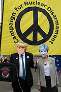 On US President Donald Trump's second day of a controversial three-day state visit to the UK, a Trump and Theresa May figures stand beneath a CND banner, as protesters voice their opposition to the 45th American President, in Trafalgar Square, on 4th June 2019, in London England.