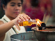 28 AUGUST 2015 - BANGKOK, THAILAND: A woman makes merit by pouring oil into a lamp at Wat Mangkon Kamalawat in the Chinatown section of Bangkok on Hungry Ghost Day. Wat Mangkon Kamalawat is the largest Mahayana Buddhist temple in Chinatown. Mahayana  Buddhists believe that the gates of hell are opened on the full moon of the seventh lunar month of the Chinese calendar, and the spirits of hungry ghosts allowed to roam the earth. These ghosts need food and merit to find their way back to their own. People help by offering food, paper money, candles and flowers, making merit of their own in the process. Hungry Ghost Day is observed in communities with a large ethnic Chinese population, like Bangkok's Chinatown.ese population, like Bangkok's Chinatown.      PHOTO BY JACK KURTZ