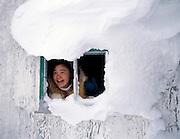 Nunavik, Grand Nord du Québec. Lors d'une expédition d'initiation à la chasse avec de jeunes Inuit, ne jeune adolescente rieuse regarde par la fenêtre d'une cabane abandonnée ayant déjà servie d'abris aux mineurs de Raglan près du village de Kangiqsujuaq.