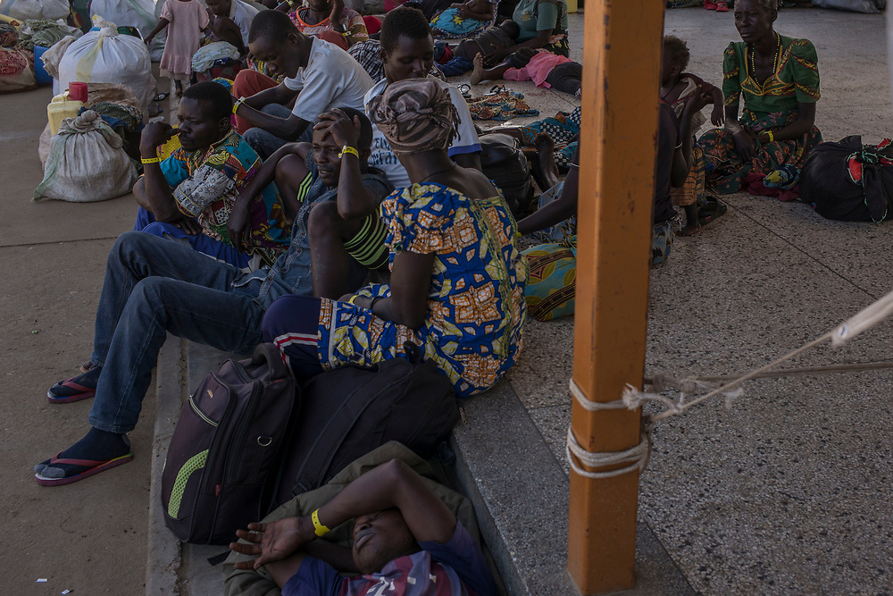 SEBAGORO, UGANDA - MARCH 22: Congolese refugees wait for transport to Kyangwali refugee settlement camp after landing in Sebagoro, Uganda on March 22, 2018. Violence in Ituri Province in northeastern Democratic Republic of Congo has displaced more than 100,000 people including approximately 40,000 refugees who have fled to Uganda. (Photo by Andrew Renneisen for The Washington Post)