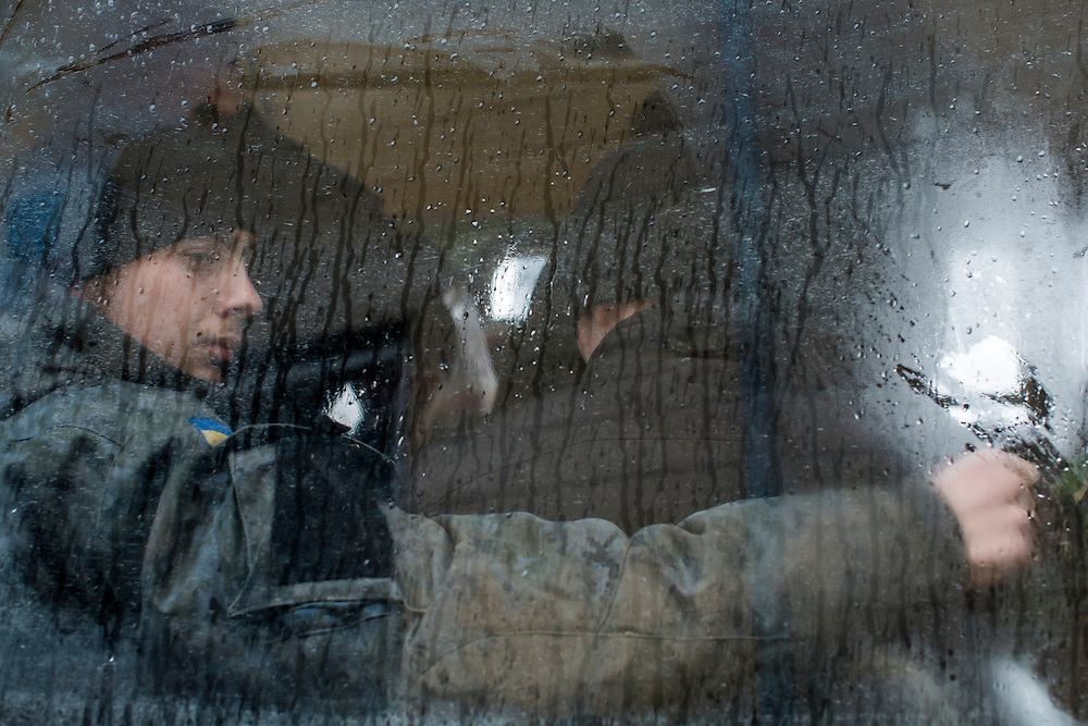 SARTANA, UKRAINE - FEBRUARY 5, 2015: After stopping at a local supermarket to stock up on snacks, Ukrainian soldiers sit on their bus on the way to front-line areas in Sartana, Ukraine. With more than 220 people having died in the past several weeks, a new diplomatic push is underway to bring an end to fighting between pro-Russia rebels and Ukrainian forces. CREDIT: Brendan Hoffman for The New York Times