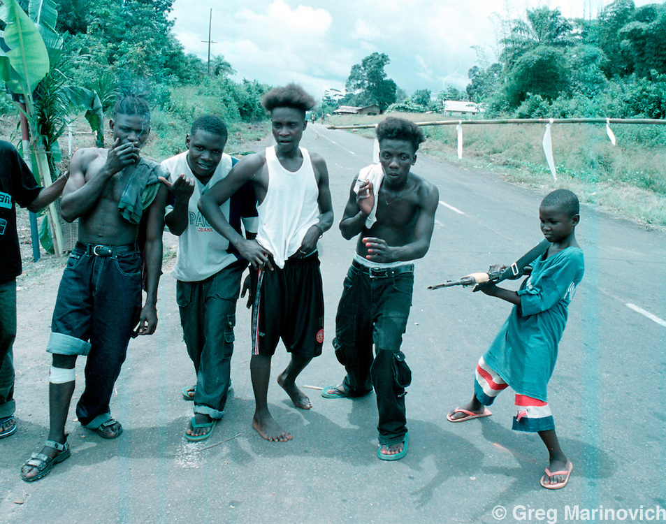 IPMG0891 Bo Waterfront, Liberia. A group of LURD rebels and child soldiers loyal to Sekouh Conneh Jr fool around at a roadblock between Monrovia and the border crossing with Sierra Leone at Bo Waterfront, Sept 22, 2003. Liberia's decades long civil conflict has destabilised the entire region and turned a generation of youth into fighters.  Greg Marinovich/South Photographs