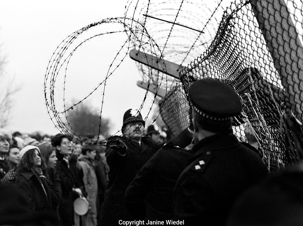 Attempting to tear down fencing at protest at The anti-nuclear Greenham Common Women's Peace Camp in 1983 / 1984. The women only camp surrounded the RAF  base in Berkshire (UK) where American cruise missiles were being stored.