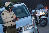 Patrol officer stands witing ticket
