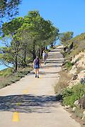 Two women walking along mountain path from Coll de Rates, Tarbena, Marina Alta, Alicante province, Spain