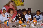 Kids and mentors painting pumpkins at Halloween party age 25 and 8 through 3.  St Paul  Minnesota USA