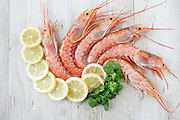 Fresh mediterranean prawns with lemon slices and parsley, flat lay.