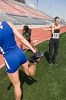 Female athletes warming up for run, low angle view