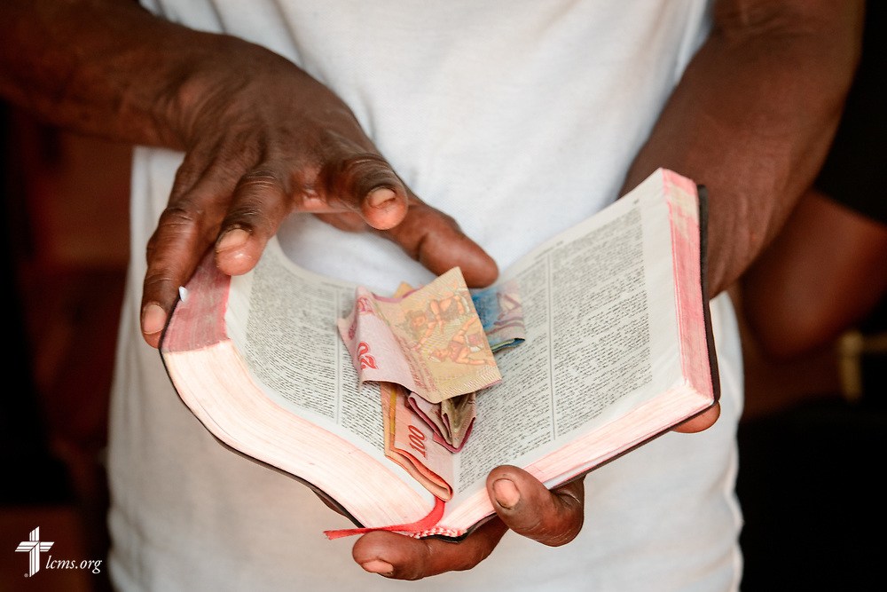 A church member uses a Bible as an improvised offertory plate during worship on the Eila rubber plantation in the Sabaragamuwa Province of Sri Lanka on Sunday, Jan. 21, 2018. LCMS Communications/Erik M. Lunsford