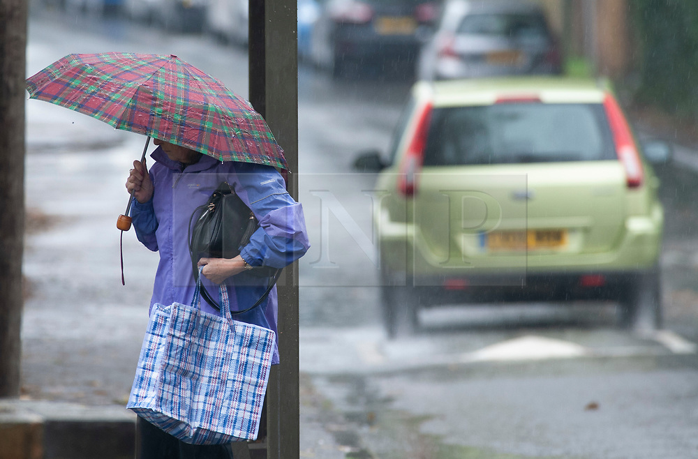 © Licensed to London News Pictures. 01/11/2018. St Mary Cray, UK.Heavy rain making for a wet weather morning in the South East. A lady stands at a bus stop with her umbrella. Photo credit: Grant Falvey/LNP