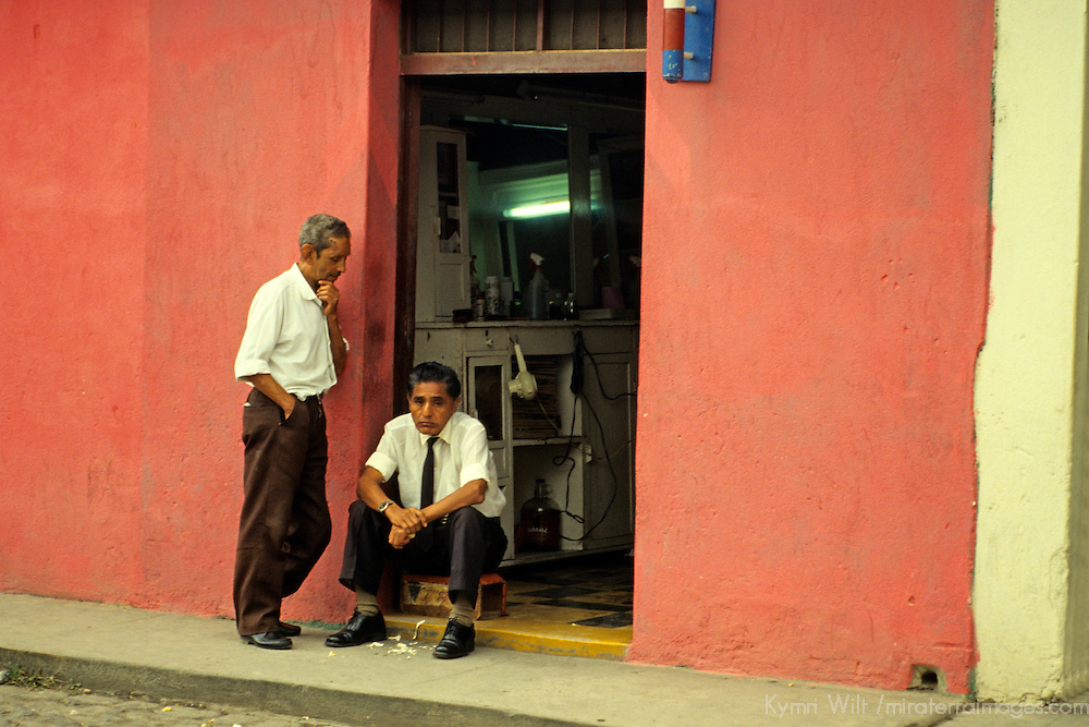 Central America, Guatemala, Antigua. Two barbers wait for business, or take a rest from it, in Antigua, Guatemala.