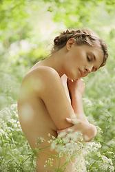 Nude Woman Hugging herself in Meadow