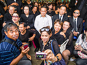 19 OCTOBER 2014 - BANG BUA THONG, NONTHABURI, THAILAND: JATUPORN PROMPAN (center, white shirt), a prominent Red Shirt leader, sits with Red Shirt supporters at Apiwan Wiriyachai's cremation at Wat Bang Phai in Bang Bua Thong, a Bangkok suburb, Sunday. Apiwan was a prominent Red Shirt leader. He was member of the Pheu Thai Party of former Prime Minister Yingluck Shinawatra, and a member of the Thai parliament and served as Yingluck's Deputy Prime Minister. The military government that deposed the elected government in May, 2014, charged Apiwan with Lese Majeste for allegedly insulting the Thai Monarchy. Rather than face the charges, Apiwan fled Thailand to the Philippines. He died of a lung infection in the Philippines on Oct. 6. The military government gave his family permission to bring him back to Thailand for the funeral. His cremation was the largest Red Shirt gathering since the coup.     PHOTO BY JACK KURTZ