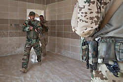 © Licensed to London News Pictures. 09/03/2015. Erbil, Iraq. Kurdish peshmerga fighters practice clearing rooms, watched by their German army instructor (left), during  an urban warfare training session at a partially finished housing estate near Erbil, Iraq. <br /> <br /> The training is part of a four week platoon level infantry training package run by coalition forces aimed at improving the efficiency of the Iraqi Security Forces. Photo credit: Matt Cetti-Roberts/LNP