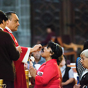 MEXICO CITY, MEXICO --A woman receving communion during Mass at the Altar of Forgiveness in the Metropolitcan Cathedral. Built in stages from 1573 to 1813, the Mexico City Metropolitan Cathedral is the largest Roman Catholic cathedral in the Americas. It sits in the heart of the historic quarter of Mexico City along one side of the the Zocalo.