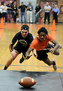 LOWER MAKEFIELD, PA - MARCH 22:  A black team member and an orange team member dive for the football during Grab Ball at Pennsbury High School's 66th annual sports nite at Charles Boehm Middle School March 22, 2014 in Lower Makefield, Pennsylvania. 11th and 12th grade students divide up into teams of black & orange (grouped by their physical education classes) and compete in a friendly rivalry through relays, skits, dances, artistic murals, cheers, and team organization. (Photo by William Thomas Cain/Cain Images)