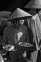 Old woman carrying plates of fish in the fish market.
