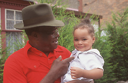 Grandfather standing outside holding young girl smiling,