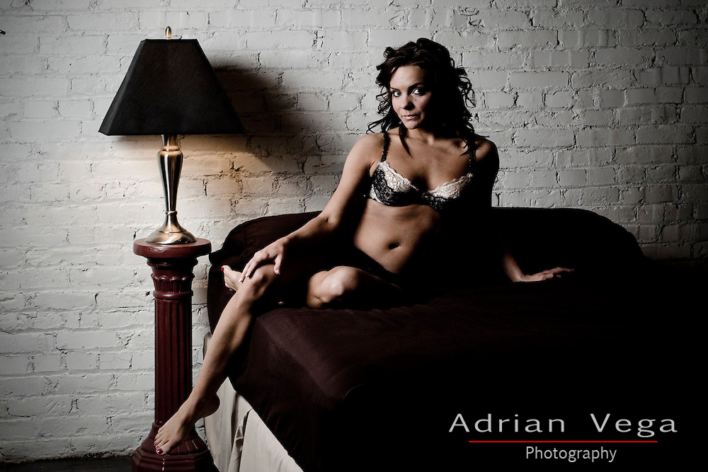 Woman in lingerie in a bedroom with a brick wall, in the midwest