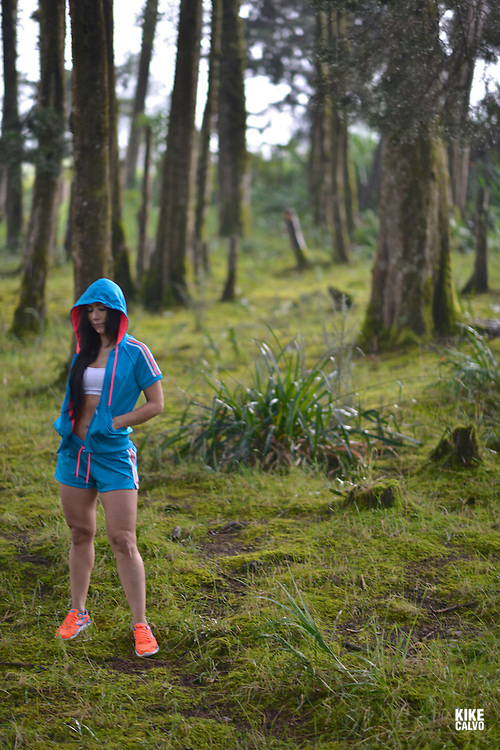 Hispanic woman in her forties exercising fitness workout in a forest and covering her face with a hoody.   May 29, 2014. (Kike Calvo via AP Images)