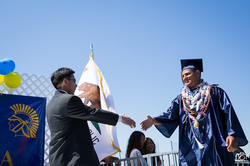 Angel Alvarez shakes hands with MUSD Board of Education member Danny Lau during the graduation ceremony at Milpitas High School in Milpitas, California, on June 6, 2015. (Stan Olszewski/SOSKIphoto)