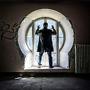 a man in front of an old window in an abandoned building