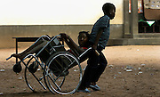 A young boy helps his disabled sister in her wheelchair across the sandy playground after classes at a Primary School in Mausse, Mozambique. (2005)